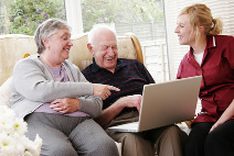 elderly couple and care worker using laptop having fun and laughing